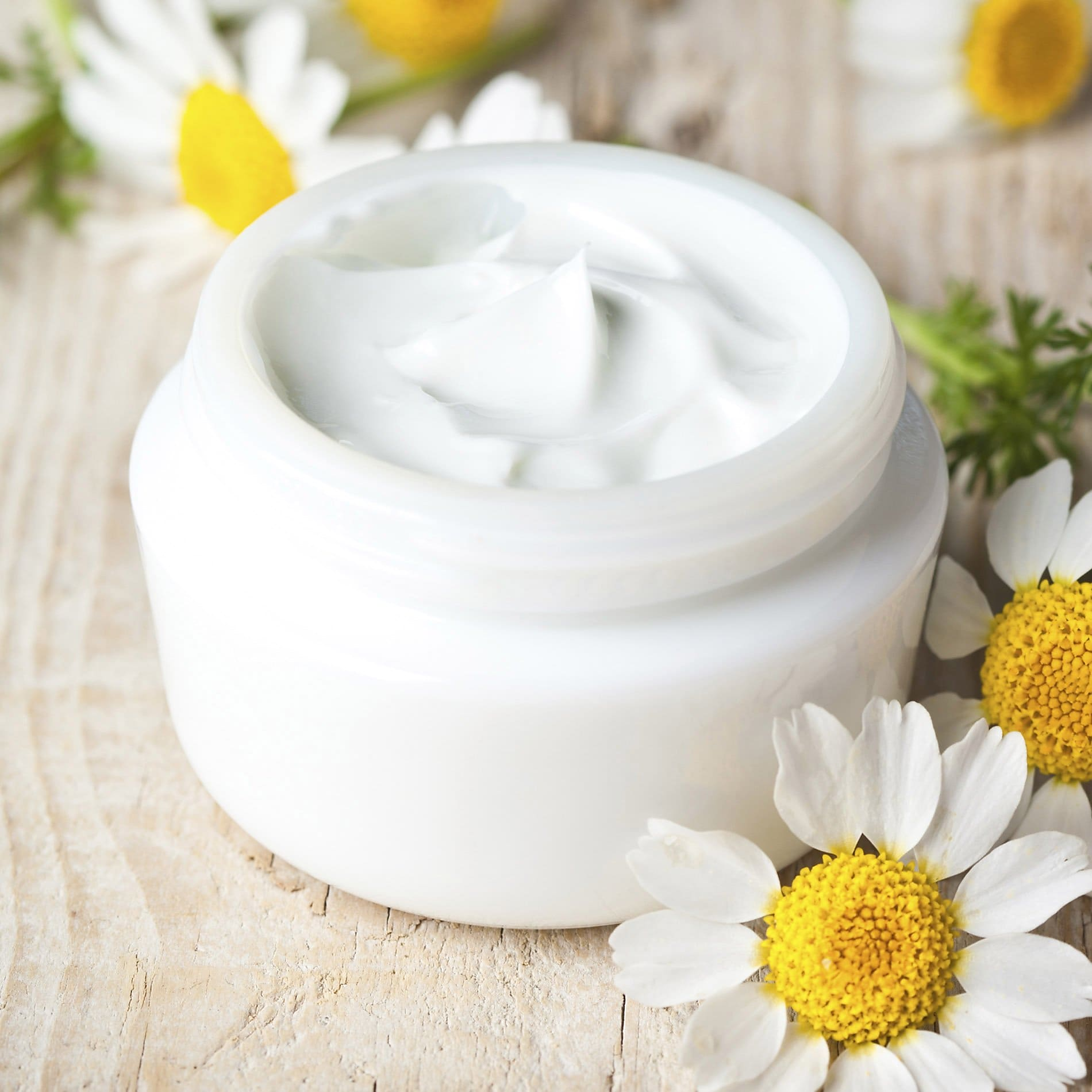 A tub of white face cream on a table surrounded by flowers