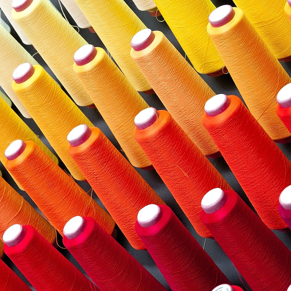 Multiple cones of cotton threads in different colours