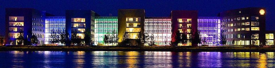A set of lit office buildings reflect off the water at night