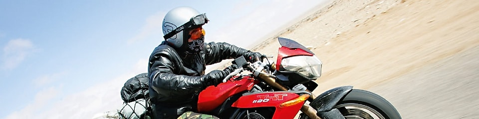 Gary Inman riding a motorbike through the dessert