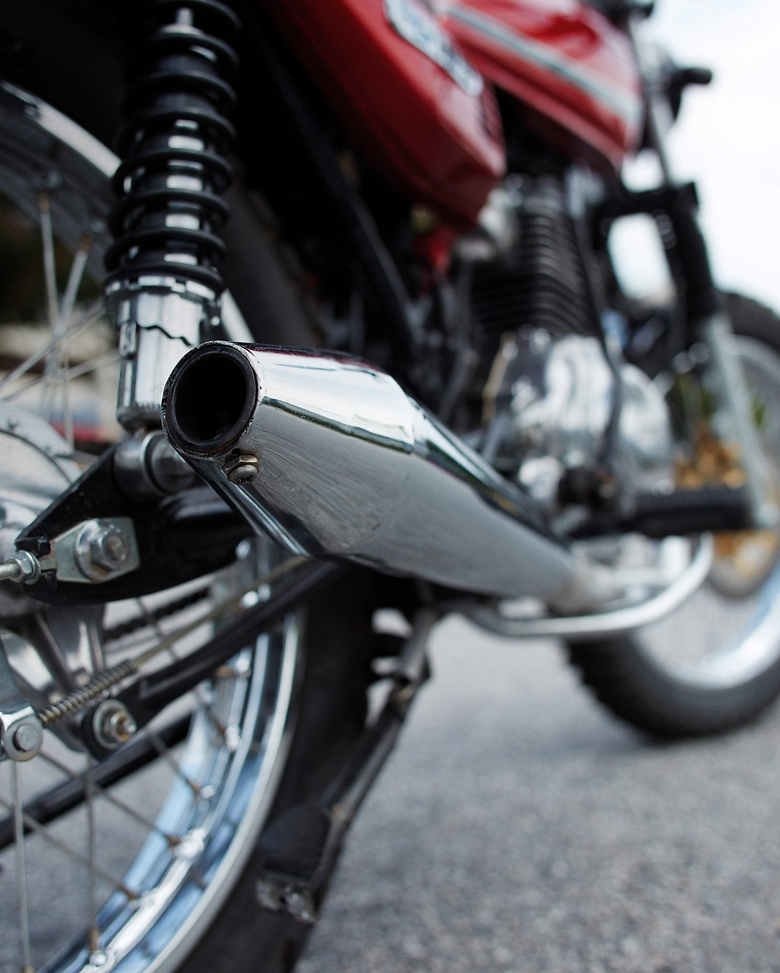 motorcycle parked on road with camera focused on the exhaust and wheels