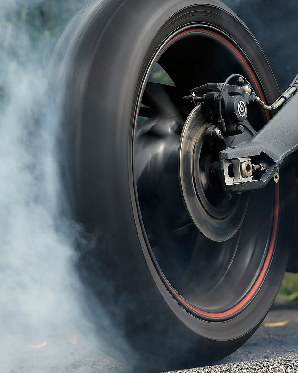 spinning motorcycle wheel producing a cloud of smoke