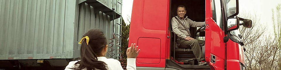 Man in red truck cab with door open waving to his daughter